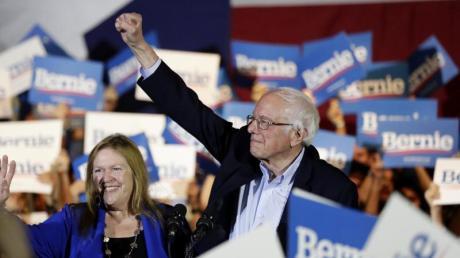Bernie Sanders und seine Frau Jane stehen bei einer Wahlkampfveranstaltung inmitten von Anhängern.