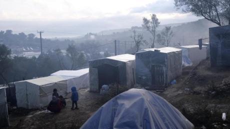 Kinder stehen nach einem Regenguss vor provisorisch errichteten Zelten außerhalb des Flüchtlingslagers Moria auf Lesbos. In und um die Registrierungslager harren mehr als 42.000 Menschen aus.