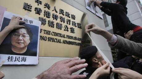 Demonstranten versuchen bei einer Kundgebung ein Foto des Hongkonger Buchhändlers Gui Minhai aus Protest gegen seine Verhaftung am Regierungssitz zu befestigen.