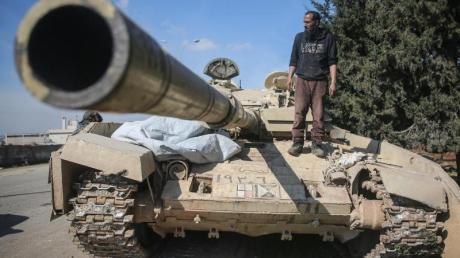 Ein Kämpfer der Nationalen Befreiungsfront (NFL) steht auf einem Panzer der syrischen Regierungstruppen.