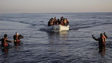 Freiwillige Helfer nehmen auf der griechischen Lesbos ein kaum seetüchtiges Gummiboot mit Flüchtlingen aus der Türkei in Empfang.