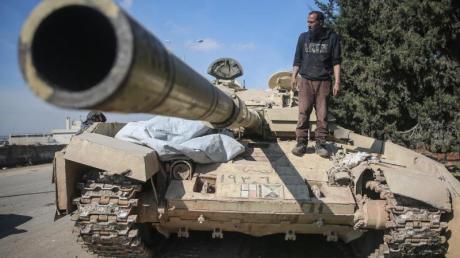 Ein Kämpfer der Nationalen Befreiungsfront (NFL) steht auf einem zurückgelassenen Panzer der syrischen Regierungstruppen.