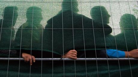 Flüchtlinge stehen im Spätsommer 2015 in einer Flüchtlingsunterkunft in Hamburg hinter einem Zaun.