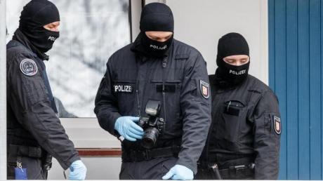 SEK-Beamte stehen während einer Razzia vor einer Wohnung in Bad Segeberg.