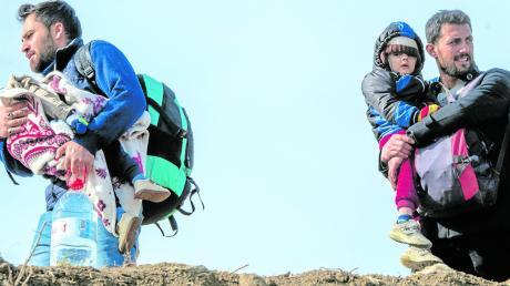 Flüchtlinge tragen ihre Kinder und Habseligkeiten in der türkischen Region Edrine Richtung griechische Grenze.
