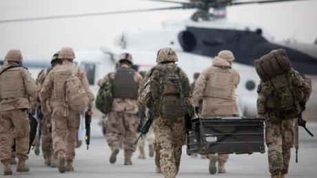 Bundeswehrsoldaten (r) auf dem Weg zu einem zivilen Hubschrauber. Die Nato will nach der Unterzeichnung eines USA-Taliban-Abkommens über Wege zum Frieden in Afghanistan ein Viertel ihrer Truppen aus dem Land abziehen.