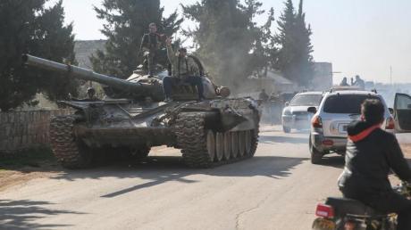 Kämpfer der oppositionellen Nationalen Befreiungsfront sind mit einem Panzer in der Region Idlib unterwegs (Archiv). Im Osten der Region ist es kurz nach Beginn der Waffenruhe zu Kämpfen zwischen Regierungsanhängern und ihren Gegnern gekommen.