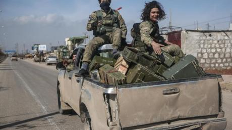 Kämpfer der Nationalen Befreiungsfront patrouillieren auf einer Straße.