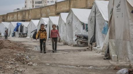 Zwei Kinder gehen an der provisorischen Zeltstadt vorbei.
