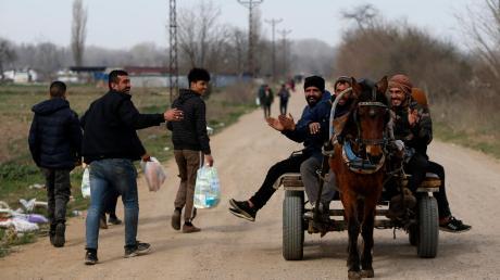 Migranten werden in der Nähe der türkisch-griechischen Grenze auf einem Karren von einem Pferd gezogen.