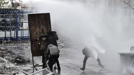 Migranten gehen an der griechisch-türkischen Grenze bei Zusammenstößen mit der griechischen Polizei in Deckung (Archiv).