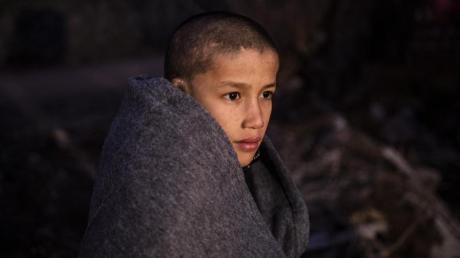 Ein Junge sitzt in Decken eingewickelt in der Nähe eines Dorfes auf Lesbos. Mehrere EU-Staaten, unter ihnen Deutschland, wollen Griechenland mindestens 1600 unbegleitete minderjährige Migranten und andere Flüchtlinge abnehmen.