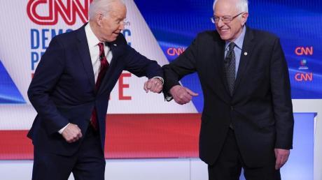 Bernie Sanders (r), und Joe Biden begrüßen sich mit ihren Ellenbogen.
