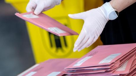 Wahlhelfer bereiten in München die Auszählung der Briefwahl vor.