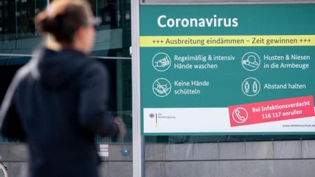 Ein Plakat informiert vor dem Bundespresseamt über Schutzmaßnahmen zum Coronavirus.