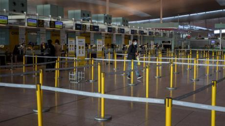 Ein Mann mit Mundschutzmaske im leeren Terminal eines Flughafens.