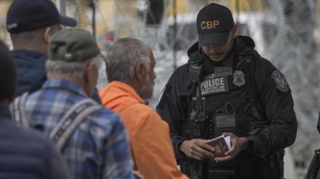 Ein Grenzbeamter kontrolliert in Tijuana am Grenzübergang zwischen Mexiko und den USA einen Pass.