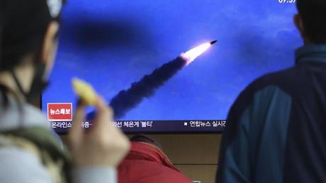 Menschen im Bahnhof von Seoul verfolgen eine Nachrichtensendung, in der über den Abschuss der Raketen berichtet wird.