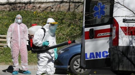 Ein Mann, der Schutzkleidung trägt, desinfiziert in Belgrad einen Krankenwagen. Serbien will die Ausbreitung des Coronavirus mit rigorosen Maßnahmen unterdrücken. Wer das Sars-CoV-2-Virus trägt, aber keine oder nur leichte Symptome hat, soll künftig strikt isoliert werden.