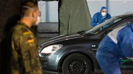 Ein Arzt nimmt bei einer von der Bundeswehr organisierten Drive-In-Teststation in Saarbrücken Abstriche.
