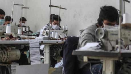 Arbeiter in der umkämpften Region Idlib mit Gesichtsmasken. In einem kleinen Labor stellen sie notdürftig Schutzmasken her.