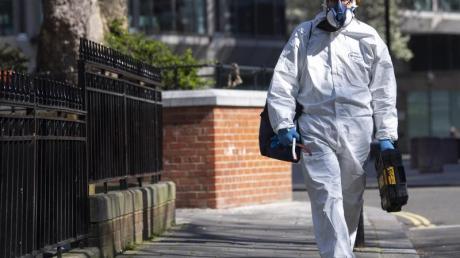 Ein Mann geht im Schutzanzug über eine Straße in Westminster im Zentrum Londons.