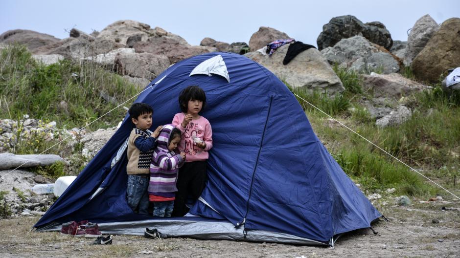 Drei Flüchtlingskinder stehen vor einem Zelt im Dorf Petra auf der nordöstlichen Ägäisinsel Lesbos.