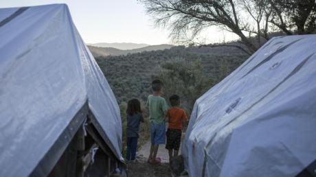 Kinder stehen zwischen Zelten in einem provisorischen Flüchtlingslager auf Lesbos.