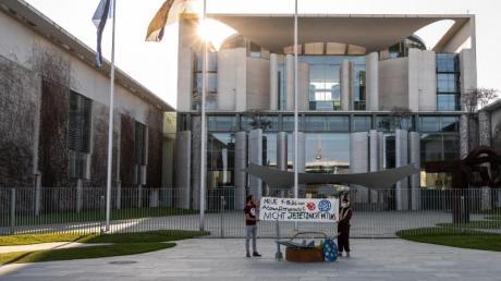 Zwei Demonstranten stehen bei einer Protestaktion gegen die Anschaffung neuer Kampfflugzeuge durch die Bundesregierung vor dem Kanzleramt.