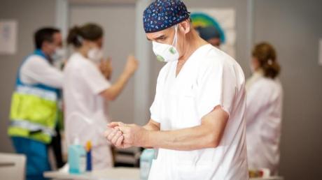 Ein Mitarbeiter des spanischen Gesundheitswesens desinfiziert seine Hände.