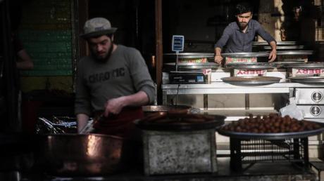 Syrische Verkäufer bereiten auf einem Straßenmarkt traditionelle Süßigkeiten zu.