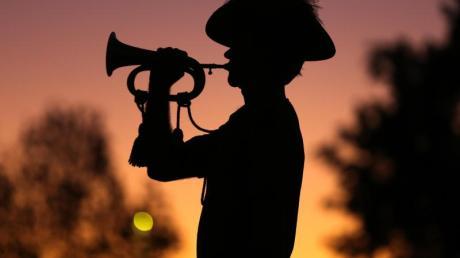 """Ein australischer Soldat spielt im Morgengrauen des ANZAC-Gedenktages """"The Last Post"""" auf der Trompete."""
