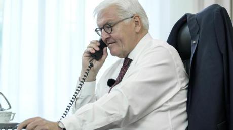 Bundespräsident Frank-Walter Steinmeier telefoniert an seinem Schreibtisch mit der Bewohnerin eines Altenheims in Bremen.