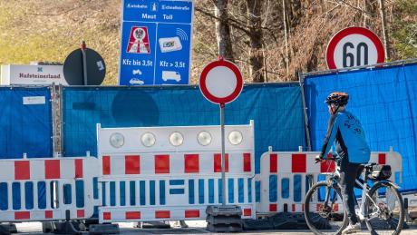 Aschau Im Chiemgau: Ein Mann mit einem Mountainbike steht auf der deutschen Seite vor der mit einem Bauzaun und blauer Plane abgesperrten Grenze zwischen dem Aschauer Ortsteil Sachrang auf bayerischer Seite und Niederndorferberg im Kufsteinerland in Tirol (Österreich).
