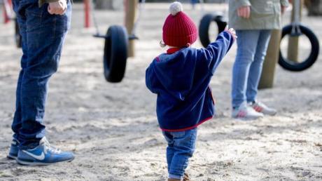 Ein Kind spielt mit seinen Eltern auf einem Spielplatz.