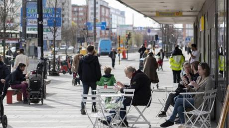 Menschen sitzen im Stadtzentrum von Stockholm vor einem Eiscafe.