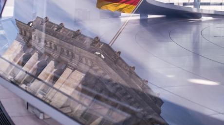 Eine Deutschland-Fahne spiegelt sich in der Kuppel des Reichstagsgebäudes.