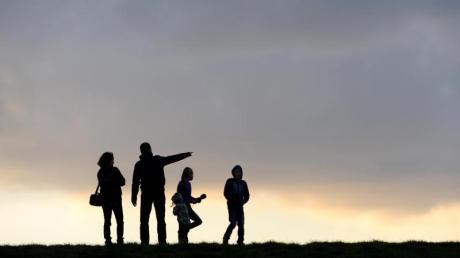 Eine Familie beim Spaziergang unterm abendlichen Wolkenhimmel.