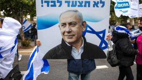 Anhänger von Ministerpräsident Netanjahu schwenken Fahnen und halten Plakate vor seiner Residenz in Jerusalem hoch.