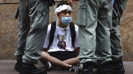 Bereitschaftspolizisten stehen im Hongkonger Central District um einen auf dem Boden sitzenden Demonstranten.