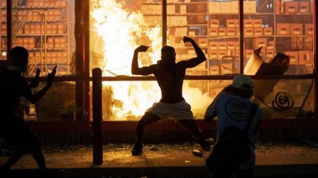 Ein Mann posiert während der gewaltsamen Proteste in Minneapolis vor einem Feuer einem Geschäft.