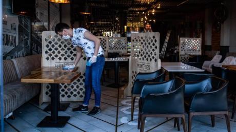 Ein Mitarbeiter reinigt die Tische eines Restaurants in Istanbul vor der Wiedereröffnung.