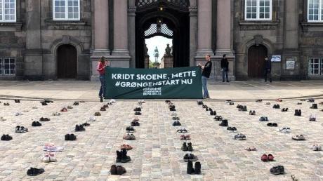 Mit in Reih und Glied aufgestellten Schuhen protestieren dänische Demonstranten vor dem Parlament in Kopenhagen für stärkere Klimaanstrengungen ihrer Regierung.