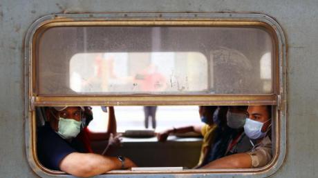 Menschen mit Gesichtsmasken sitzen in einem Zug in Kairo.