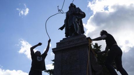 Zwei Männer befestigen ein Seil um den Hals einer Statue von Christopher Columbus.