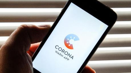 Auf dem Bildschirm eines Apple iPhone SE ist der vom Presse- und Informationsamt der Bundesregierung herausgegebene Startschirm einer Corona Warn-App abgebildet.