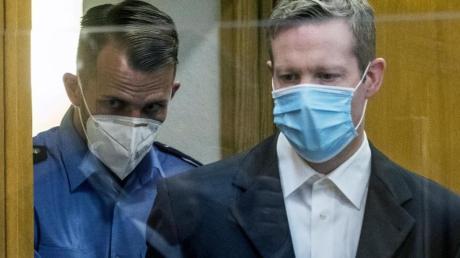 Der Angeklagte (r) wird am ersten Tag des Prozesses mit Mundschutz in einen Gerichtssaal des Oberlandesgerichts gebracht.