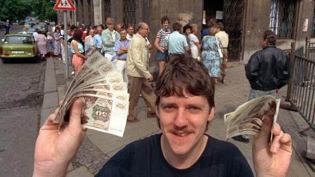 Der 1. Juli 1990 war ein historischer Tag für Deutschland: Nach langem Schlangestehen vor einer Leipziger Sparkassen-Filiale freut sich dieser Mann über seine D-Mark-Banknoten.
