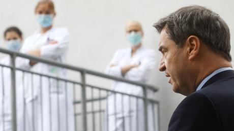Klinikpersonal verfolgt die Äußerungen von Markus Söder (CSU, recht), Ministerpräsident von Bayern, nach einem Besuch der Intensivstation in der München Klinik Schwabing.