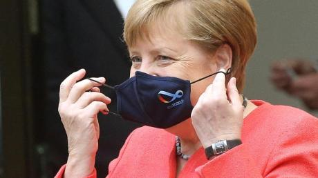 Bundeskanzlerin Angela Merkel (CDU) nimmt im Bundesrat ihre Mund- und Nasenschutzmaske ab, bevor sie eine Rede zu Zielen der EU-Ratspräsidentschaft hält.